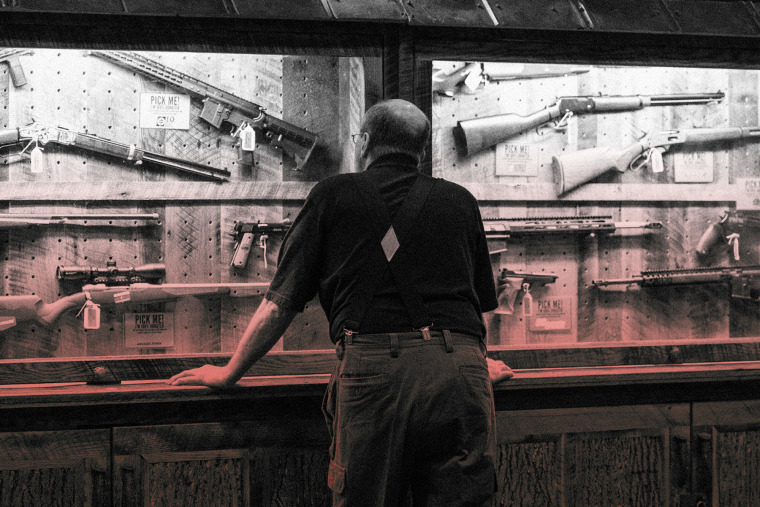 IMage: A man looks at a case of firearms at the National Rifle Association convention in Indianapolis in 2019.