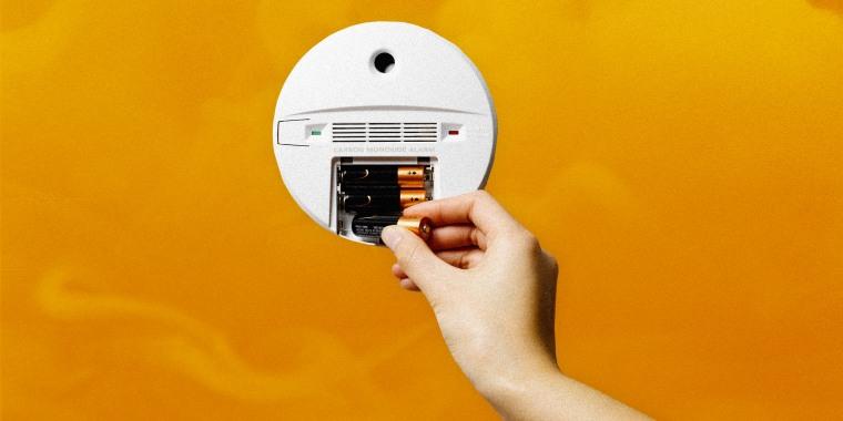 Illustration shows a hand putting batteries into a carbon monoxide detector.