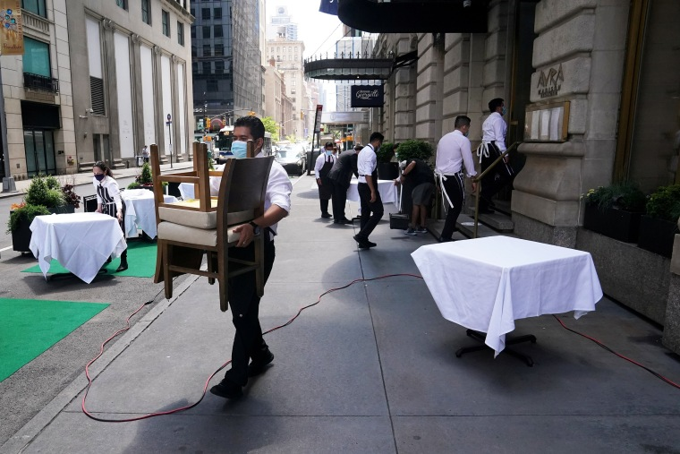A waiter sets up tables in front of a restaurant In New York on June 22, 2020.