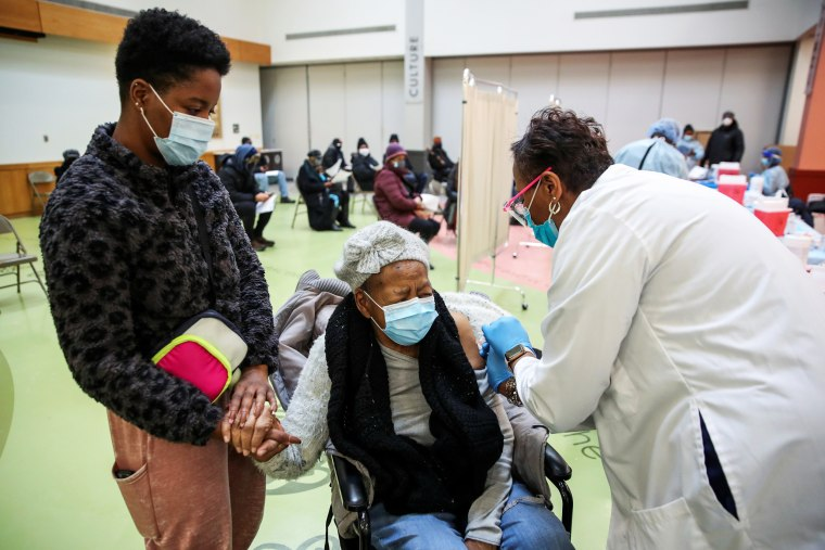 Juanta J. Gordon receives the Moderna Covid-19 vaccination from her daughter, nurse Zyra D. Gordon Smith, at Trinity United Church of Christ in Chicago on Feb. 13, 2021.