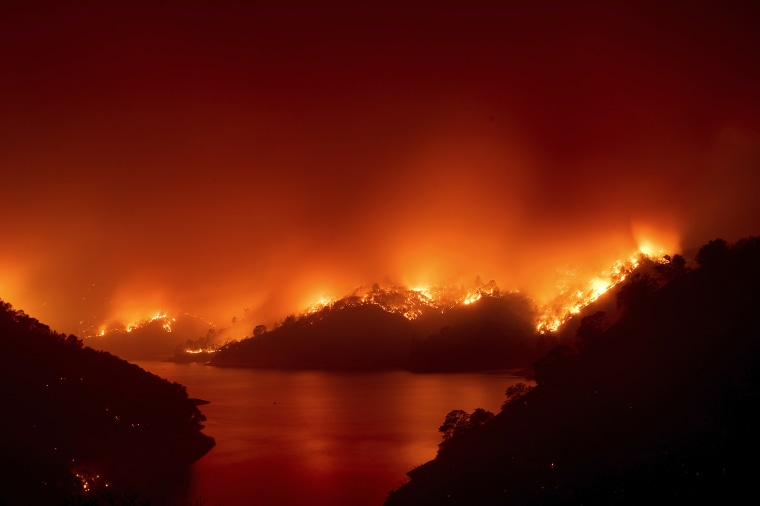 Image: Flames from the LNU Lightning Complex fires burn around Lake Berryessa in unincorporated Napa County, Calif., on Wednesday, Aug. 19, 2020. Fire crews across the region scrambled to contain dozens of wildfires sparked by lightning strikes.
