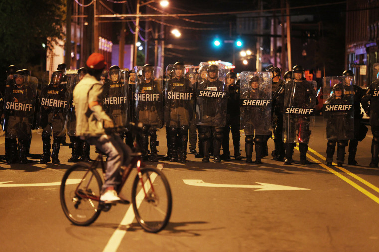 Law enforcement officials in riot gear force people off a street as they protest the killing of Andrew Brown Jr. on April 28, 2021, in Elizabeth City, N.C.