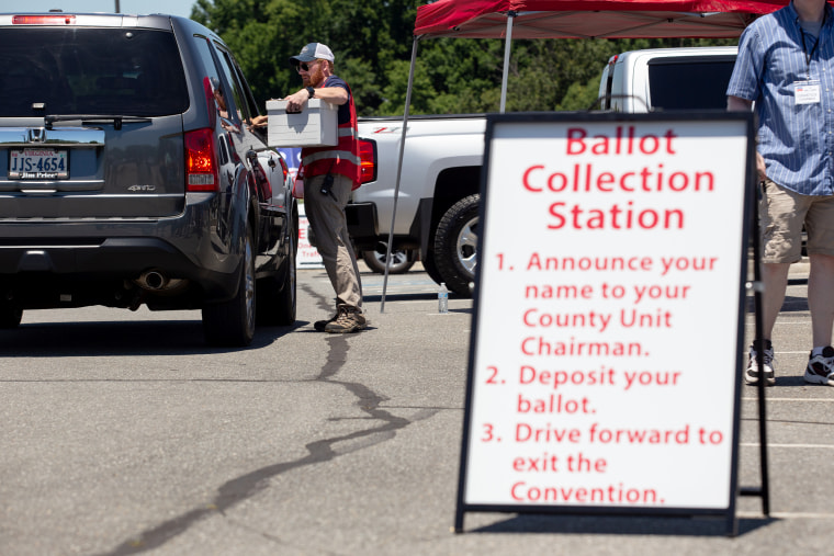 Volunteers hand out and collect ballots from delegates via drive-through lanes during the convention at Tree of Life Ministries in Lynchburg, Va., on June 13, 2020.