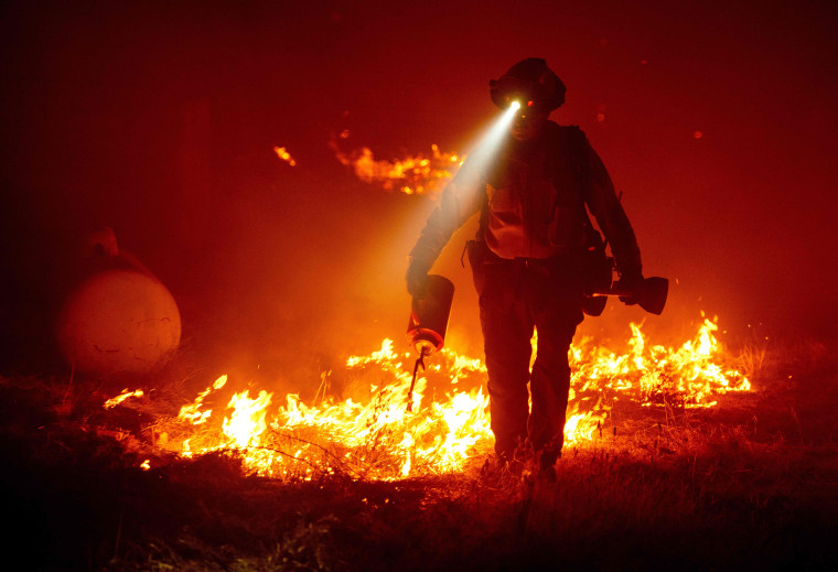 Image: Firefighters cut defensive lines and light backfires to protect structures behind a CalFire fire station during the Bear fire,
