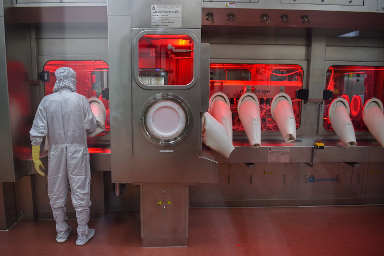 Image: An employee in protective gear works on an assembly line for manufacturing vials of Covishield, AstraZeneca-Oxford's Covid-19 coronavirus vaccine at India's Serum Institute in Pune, India
