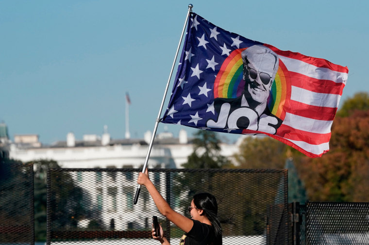 Image: A woman waves a Joe Biden flag as people celebrate on Black Lives Matter plaza across from the White House Nov. 7, 2020, after Joe Biden was declared the winner of the 2020 presidential election.