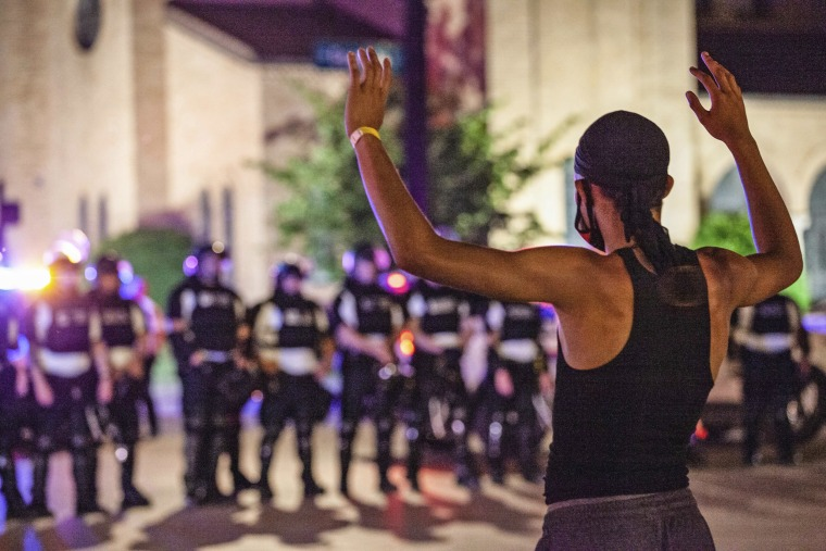 A protester puts his hands up in front of a line of Columbus Police Officers in riot gear on June 5, 2020.