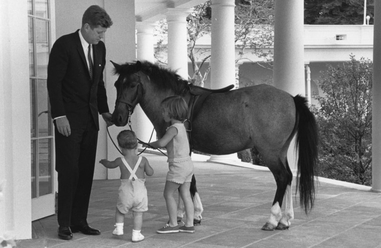 Image; Outside of the Oval Office, President John F. Kennedy and his children, John and Caroline, play with their pet pony, Macaroni, in 1962.