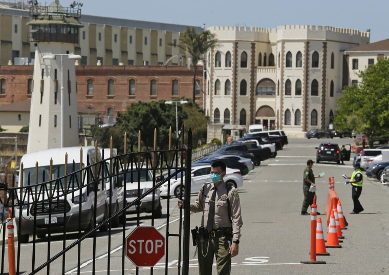 Image:; A correctional officer closes the main gate at San Quentin State Prison in San Quentin, Calif., on July 9, 2020.