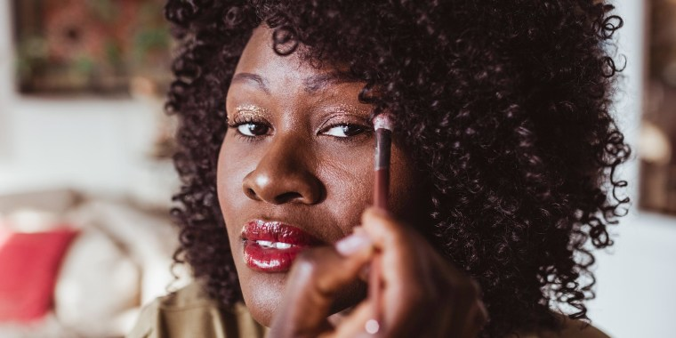 Woman applying eyeshadow with brush at home