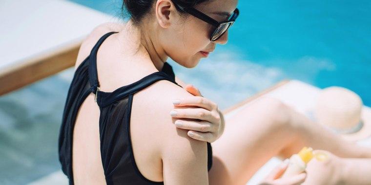 Woman applying suntan lotion while sunbathing by the swimming pool