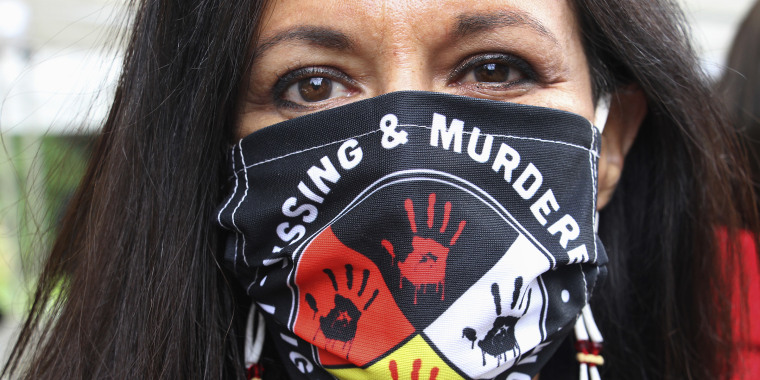 Jeannie Hovland, the deputy assistant secretary for Native American Affairs for the U.S. Department of Health and Human Services, poses with a Missing and Murdered Indigenous Women mask, in Anchorage, Alaska on Aug. 26, 2020.