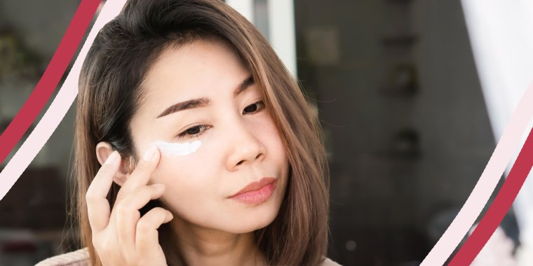 Woman rubbing eye cream under her eye, while looking in the mirror