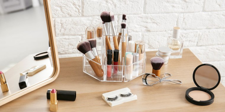 Makeup cosmetic products and tools on dressing table, with an acrylic lazy Susan organizer. Best makeup organizers and storage ideas, including acrylic makeup organizers from Amazon, Walmart, Target, iDesign, The Container Store and more.