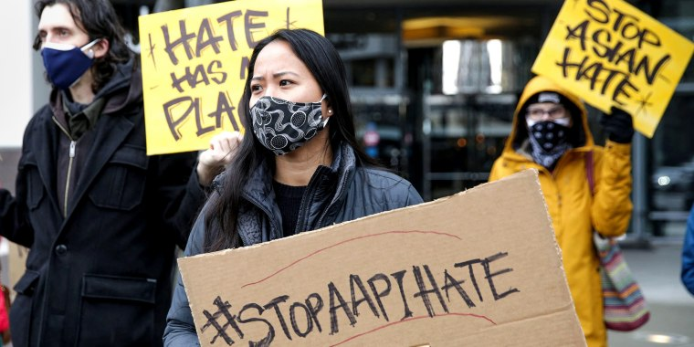 """Trish Villanueva, center, of Seattle holds a sign with the hashtag """"Stop AAPI hate"""" during the We Are Not Silent rally organized by the Asian American Pacific Islander Coalition Against Hate and Bias in Bellevue, Wash., on March 18."""