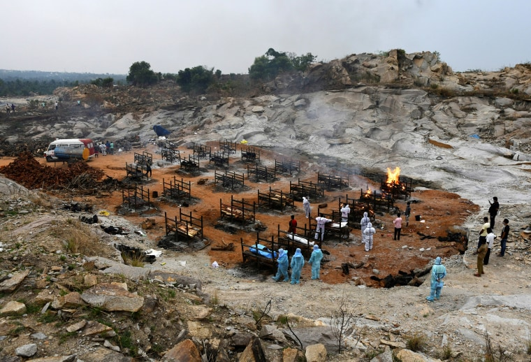 Image: Volunteers and relatives prepare to cremate the bodies of people who died due to Covid-19 at a crematorium ground in Giddenahalli village on the outskirts of Bengaluru