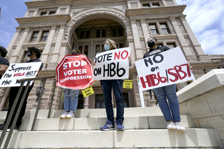 Image: People opposed to Texas voter bills HB6 and SB7 hold signs during a news conference hosted by Texas Rising Action on the steps of the State Capitol on April 21, 2021, in Austin, Texas.