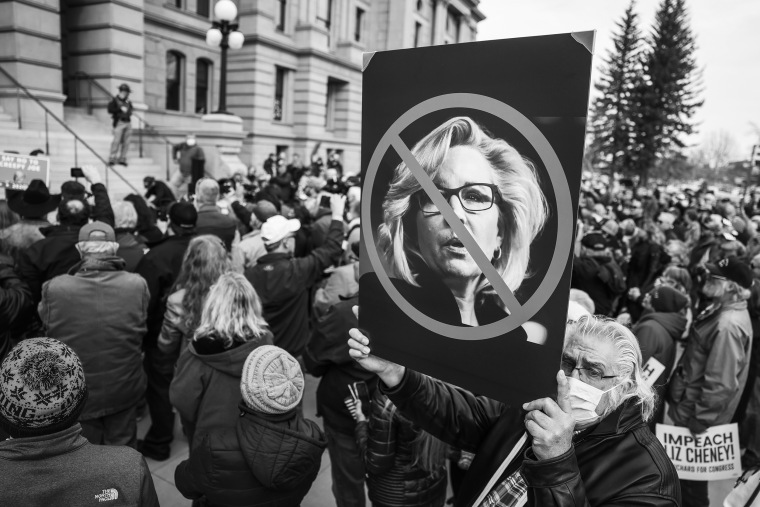 Image: A man holds up a sign against Rep. Liz Cheney, R-Wyo., as Rep. Matt Gaetz, R-Fla., speaks to a crowd during a rally against her on Jan. 28, 2021 in Cheyenne, Wyo.