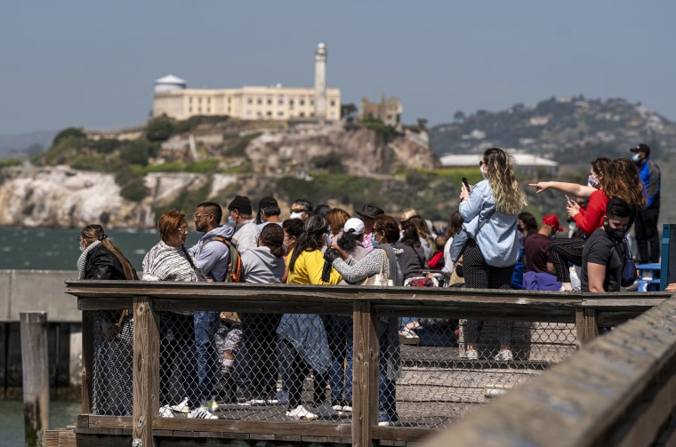Image: Visitors stand on Pier 39 in front of Alcatraz Island in San Francisc
