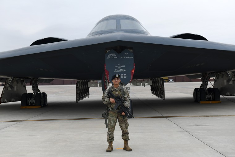 Security Forces Defender Airman 1st Class Elijah R. Posana stands in front of B-2 Spirit
