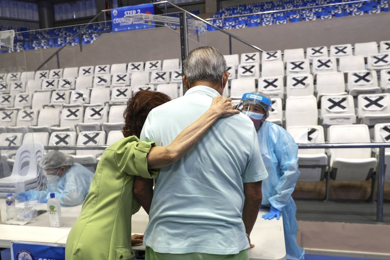 Image: An elderly couple talks to a health worker at a vaccination center inside the Makati Coliseum in Manila, Philippines