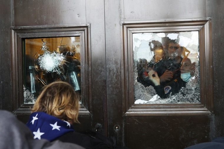 Image: A Capitol police officer looks out of a broken window as protesters gather on the U.S. Capitol Building