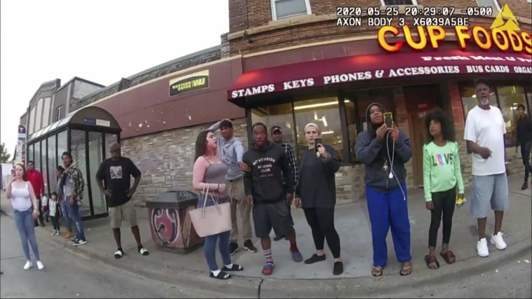 A police body camera shows bystanders including Alyssa Funari, left filming, Charles McMillan, center left in light colored shorts, Christopher Martin center in gray, Donald Williams, center in black, Genevieve Hansen, fourth from right filming, Darnella Frazier, third from right filming, as former Minneapolis police officer Derek Chauvin was recorded pressing his knee on George Floyd's neck for several minutes in Minneapolis on May 25, 2020.