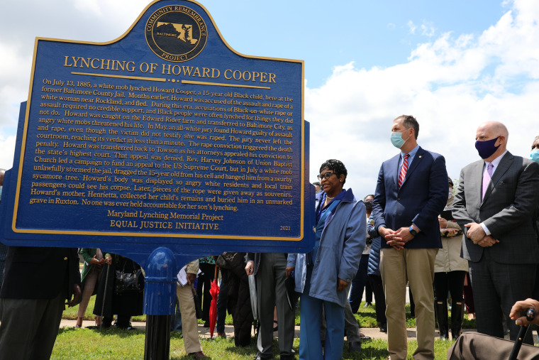Maryland Gov. Larry Hogan, right, Baltimore County Executive John Olszewski and Maryland House Speaker Adrienne Jones stand next to a new historic marker on May 8, 2021, in Towson, Md.