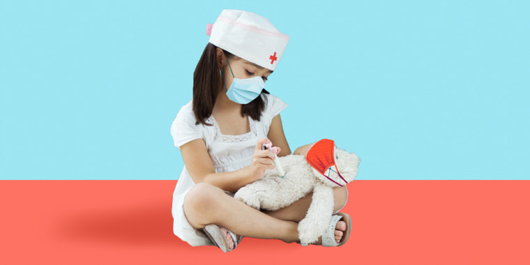 Photo illustration of little girl playing doctor with a teddy bear both wearing face masks