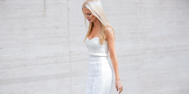 Woman wearing a white strapless top and white linen pants, walking outside