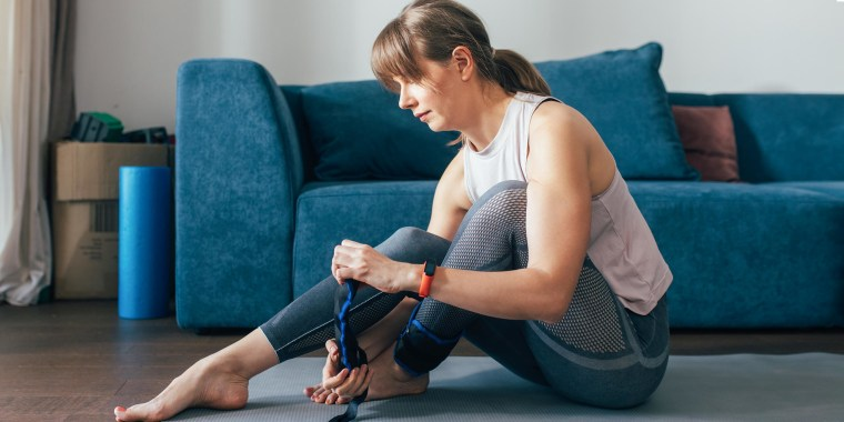 Woman sitting on the floor on a yoga mat, putting on blue ankle weights