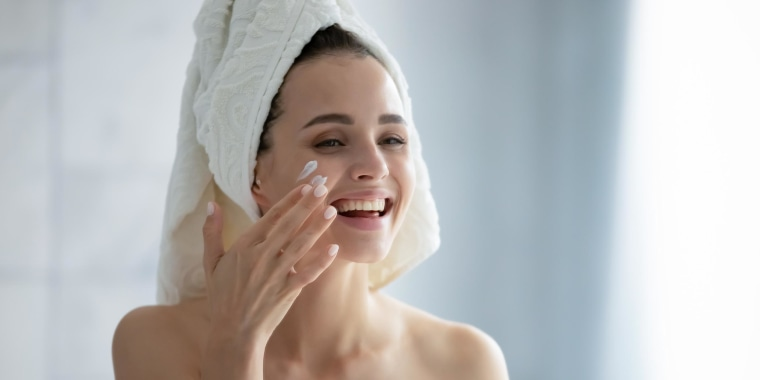 Woman applying moisturizing cream after shower on her cheek