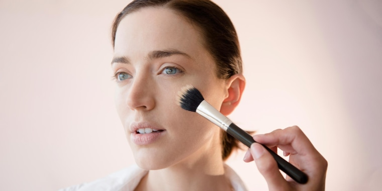 Woman applying makeup with a brush