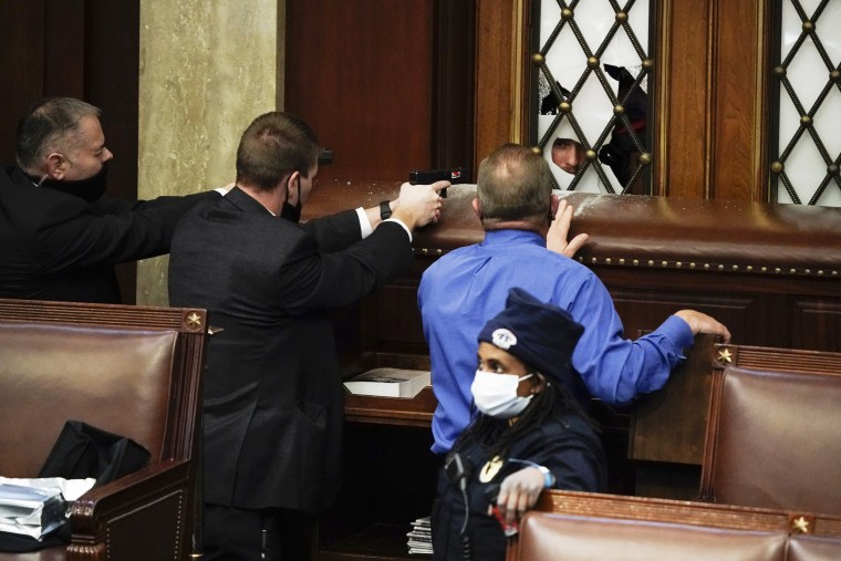 Image: Police with guns drawn watch as protesters try to break into the House Chamber on Jan. 6, 2021.