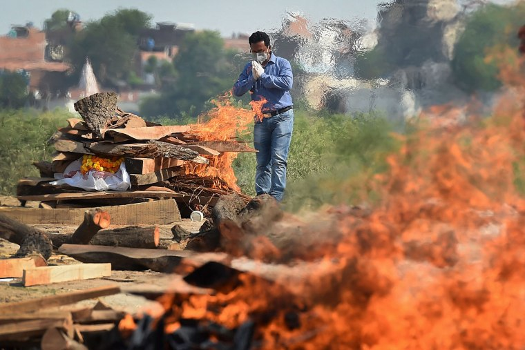Image: A family member offers prayers during cremation of his loved one who died from Covid-19 in Allahabad, India, on May 8, 2021.