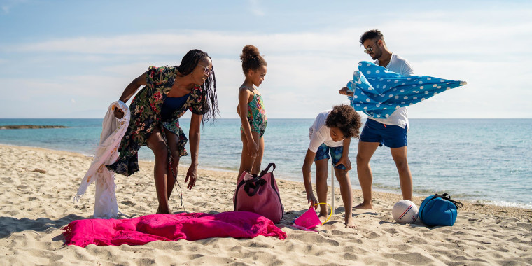 Parents and their children are settling down towels at the beach. The best beach towels include Turkish beach towels, round beach towels and microfiber beach towels from retailers such as Amazon, Target, Wayfair and more.