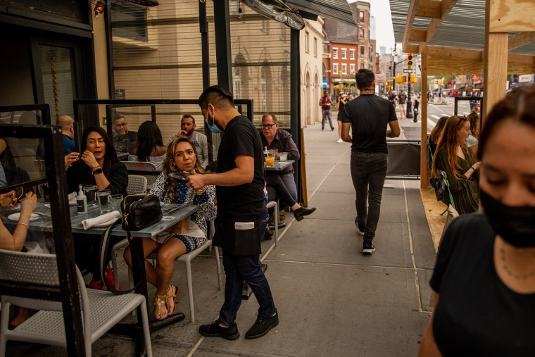 Employees assist customers in the outdoor dining area of a restaurant in the West Village neighborhood of New York on April 28, 2021.