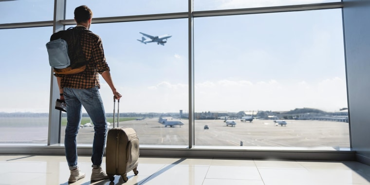 Man standing near window, holding luggage and wearing a backpack at the airport and watching plane before departure
