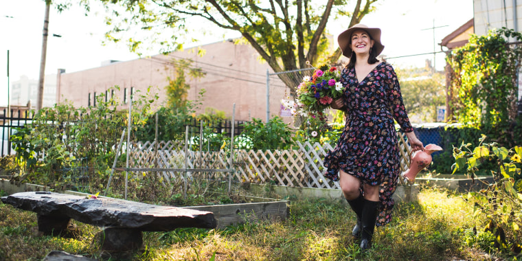 Woman walking through her garden wearing a floral dress, a hat, and holding flowers. The best dress sales and dress deals happening now from Amazon, ASOS, Macy's, Target, Madewell and more can help you find the perfect summer dress.