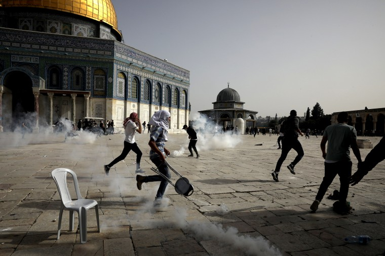 Image: Palestinians run away from tear gas during clashes with Israeli security forces at the Al Aqsa Mosque compound in Jerusalem's Old City on May 10, 2021.