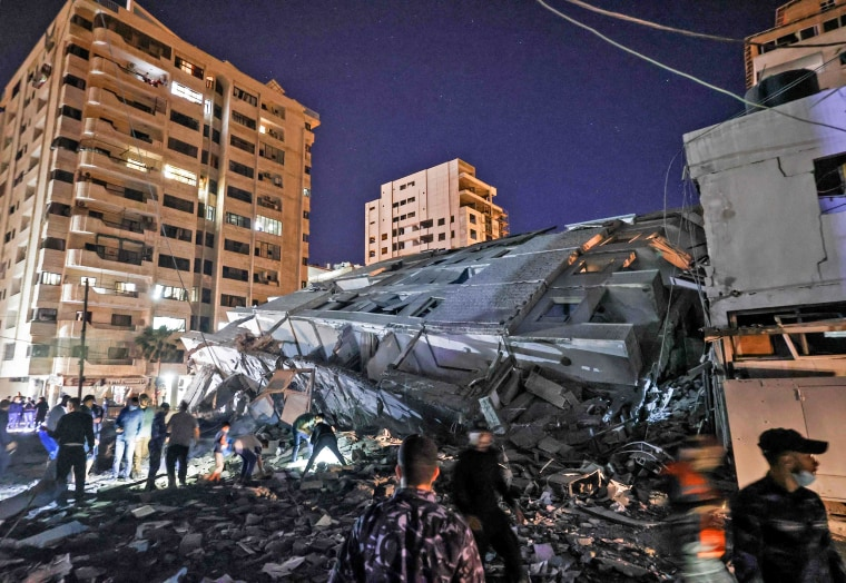 People gather at the site of a collapsed building in the aftermath of Israeli air strikes on Gaza City on May 11, 2021.