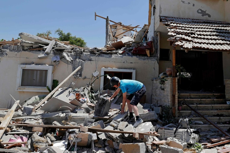 Israeli Elisha Golan, 73, looks through the rubble at her house in Yehud, central Israel, on May 12, 2021, after rockets were fired by the Hamas movement from the Gaza Strip.