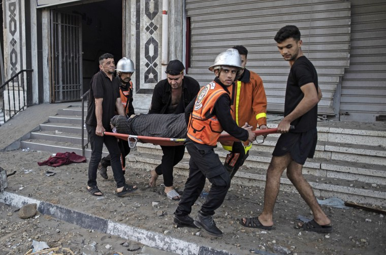 Image: Palestinian rescuers evacuate an elderly woman from a building following Israeli airstrikes on Gaza City on May 12, 2021.