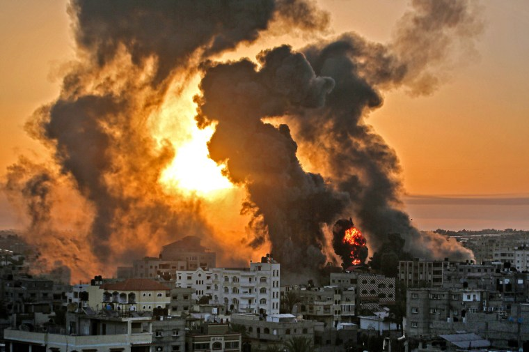 A fire rages at sunrise in Khan Yunish following an Israeli airstrike in the southern Gaza strip on May 12, 2021.