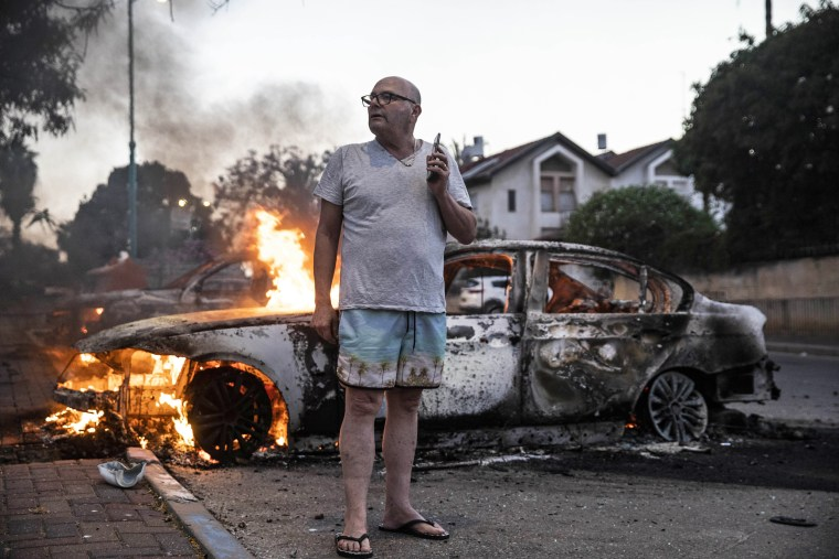 Image: Jacob Simona stands by his burning car during clashes between Israeli Arabs and police in the Israeli mixed city of Lod on May 11, 2021.