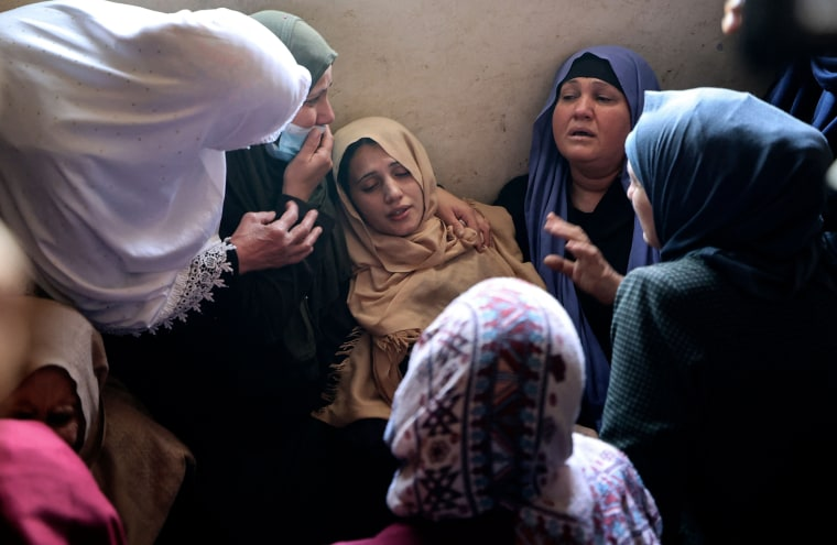 The mother of Palestinian Hussien Hamad, 11, is comforted by mourners during his funeral in Beit Hanoun in the northern Gaza Strip on May 11, 2021.