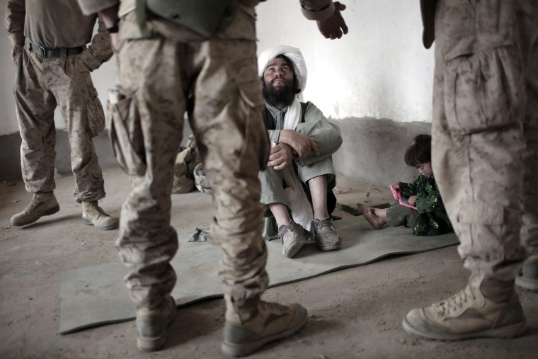 Image: A local Afghan imam listens to an interp