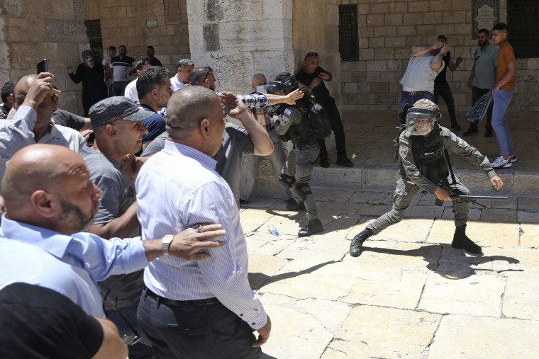 Image: Israeli border police swing their batons at Muslim worshippers gathered for Friday prayers at the Dome of the Rock Mosque in the Al-Aqsa Mosque compound in the Old City of Jerusalem on May 14.