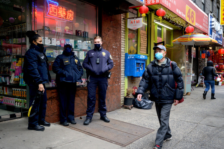 Police officers stand on a street in the Chinatown area of New York City on March 17, 2021.
