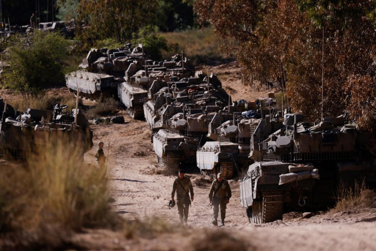 Image: Israeli soldiers walk next to tanks near the border between Israel and the Gaza Strip, on its Israeli side